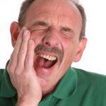 Zahnschmerzen, Mann hält sich die Wange - istockphoto.de - clu